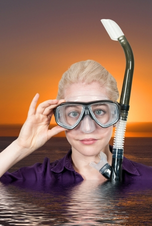 Woman in clothes in water with a snorkle and mask photo