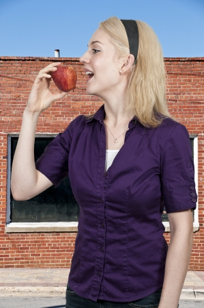 A beautiful young woman eating a fresh delicious apple photo