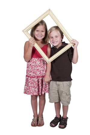 Little boy and girl looking through an ornate picture frame photo