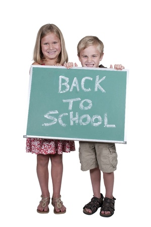 Little girl and boy holding a back to school sign on a blackboard photo