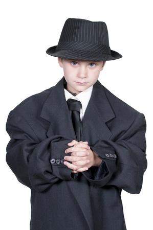 Kleine jongen gekleed in oversized pak kleren