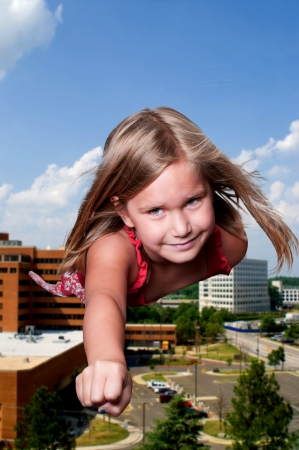 Beautiful little girl super hero flying through the sky photo