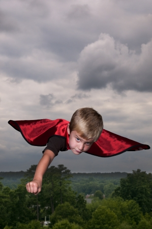 rescue imagine: Handsome young boy super hero flying through the sky