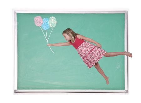 Beautiful little girl floating with balloons on a chalkboard photo