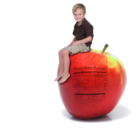 Handsome little boy sitting on a green apple with a nutrition label photo
