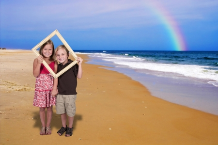Little boy and girl looking through an ornate picture frame at the beach