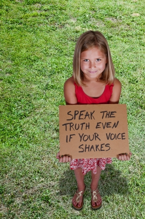 Beautiful little girl holding up an inspirational sign photo