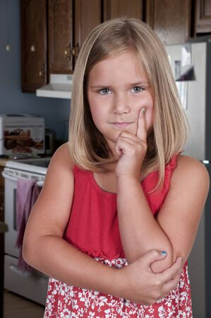 Beautiful little girl thinking and deep in thought photo