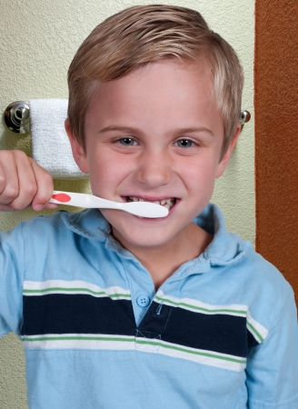 Handsome little boy exercising good dental hygiene by brushing his teeth photo