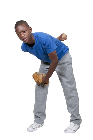 A black African American teenage man baseball pitcher getting ready to throw a ball in a game photo
