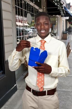 Handsome teenage black African American man eating Chinese Japanese or Asian takeout food Stock Photo - 15113114