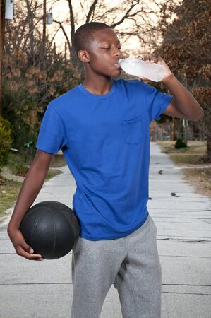 man drinking water: Young black African American teenage boy with a basketball