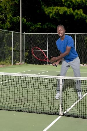 Knappe jonge zwarte Afrikaanse Amerikaanse tiener man tennis Stockfoto