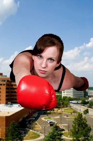 Beautiful woman super hero flying through the sky with boxing gloves Stock Photo - 15113222