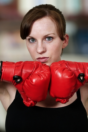 A beautiful young woman wearing a pair of boxing gloves Stock Photo - 15112833