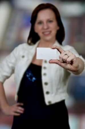 Beautiful young woman holding up a business card Stock Photo - 15113100