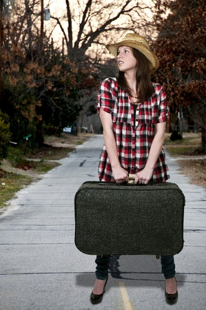 evicted: Beautiful young woman going on vacation with a suitcase Stock Photo