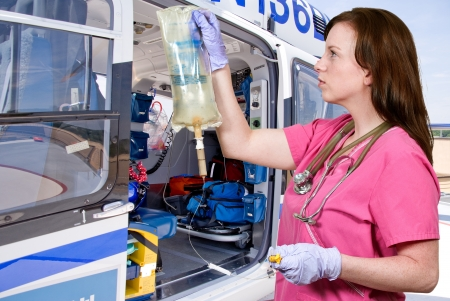 Beautiful young woman doctor holding an IV bag in front of a life flight helicopter Standard-Bild