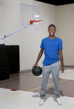 Handsome young black African American teenage man playing basketball photo