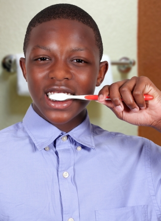 Handsome teenage boy exercising good dental hygiene by brushing his teeth Banque d'images
