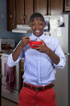 Handsome teenager eating food from a bowl photo