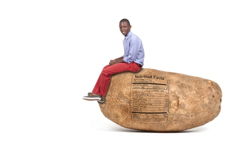 Handsome young black teenager sitting on a potato