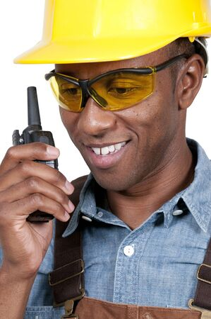 Handsome black man construction worker talking on a walkie talkie photo