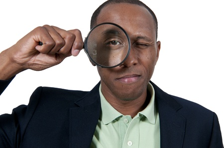 Handsome African American man looking through a large magnifying glass Stock Photo - 15646734