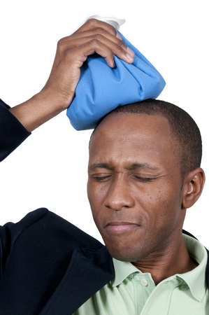 Handsome African American man using an ice pack for a headache