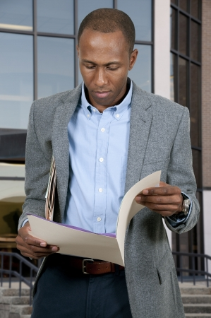 Handsome black African American business man with manilla folders full of documents photo
