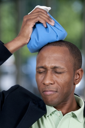 Handsome African American man using an ice pack for a headache photo