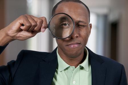lupa: Apuesto hombre afroamericano que mira a trav�s de una lupa grande
