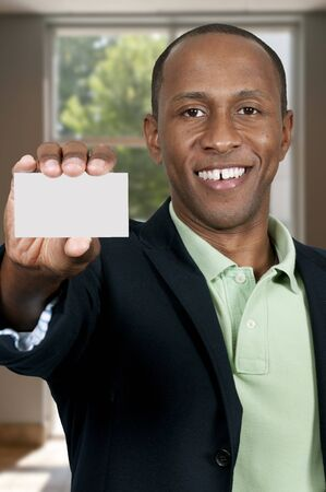 Handsome African American man holding up a business card Stock Photo - 15646735
