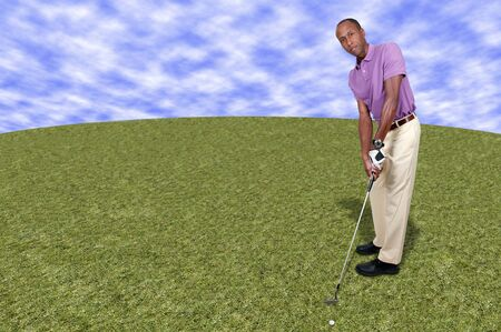 Handsome man putting and playing a round of the sport known as golf Stock Photo - 15646775