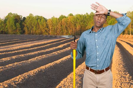 Man farmer with a hoe in the furrows of a freshly plowed field Stock Photo - 15646694