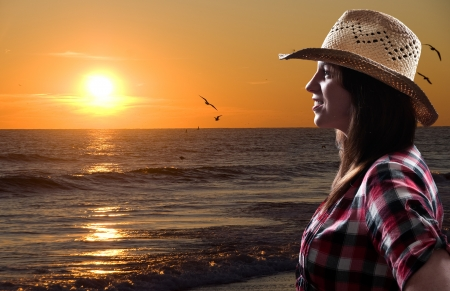 Beautiful young woman in front of a sunset photo