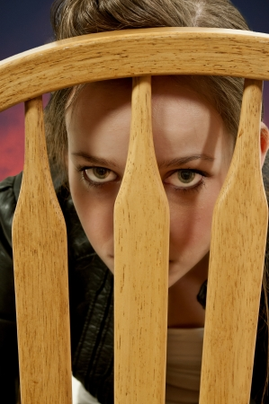 Beautiful young teenage woman hiding and looking through a chair back Stock Photo