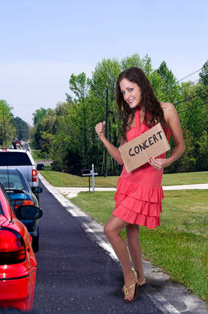 Beautiful woman with a sign hitch hiking to a concert photo