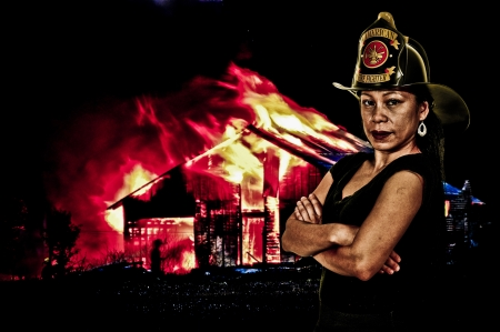 turnout gear: Beautiful young woman firefighter at a fire