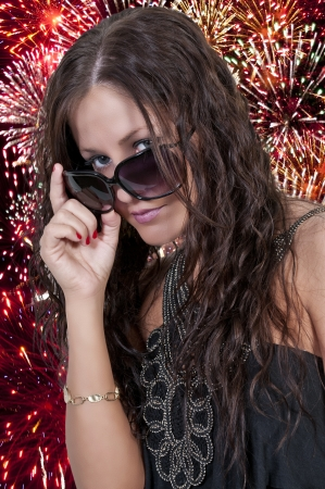 Beautiful woman holding a US flag at a fireworks display photo