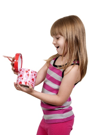 Beautiful little girl opening a Valentines day present photo