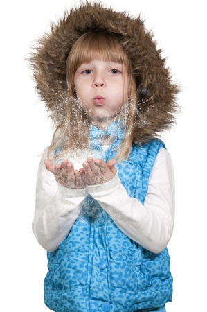 winter fashion: Beautiful little girl blowing snow off of her hands Stock Photo