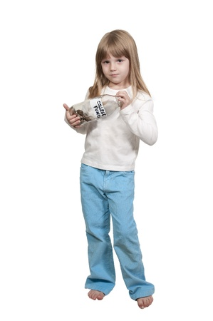 Beautiful little girl holding her college fund of coins in a milk bottle