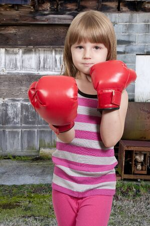 Beautiful young little girl wearing a pair of boxing gloves photo