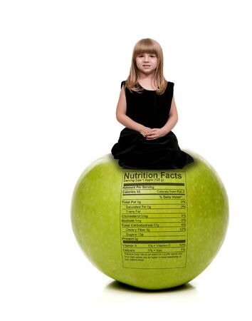 Beautiful little girl sitting on aGranny Smith green apple with a nutrition label Stock Photo - 16717664