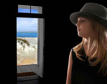 сooking: Little girl ooking at the ocean through a beach house doorway
