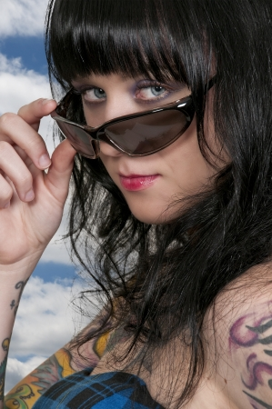 tatt: A beautiful woman wearing a pair of sunglasses Stock Photo