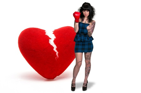 A beautiful woman in wearing a boxing glove in front of a broken heart - heartbreaker Stock Photo - 16717364