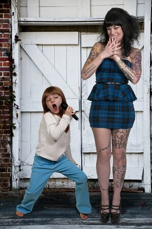 Beautiful tattooed young woman and her singing little girl Stock Photo - 16717618