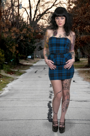 Beautiful tattooed young woman looking far away
